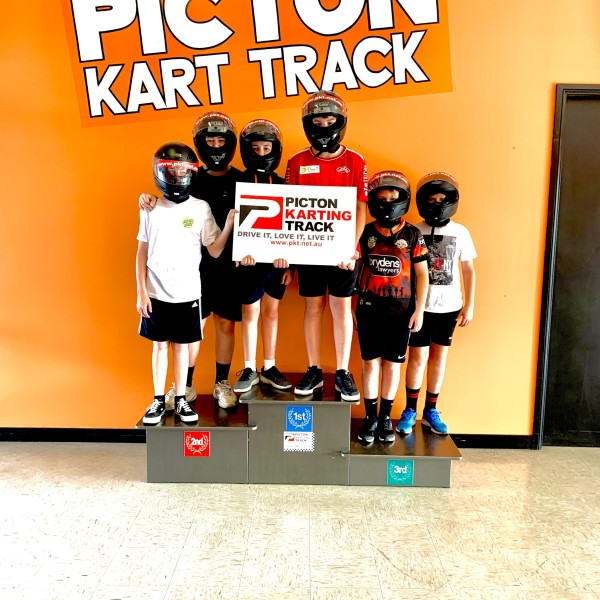 Racing track winners standing on a podium holding their certificate