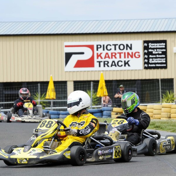 Racers riding around the go-kart track with Picton Karting Track signage in the background
